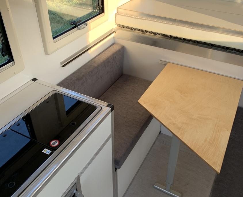 Geschlossene Wohnkabine mit Sitzgruppe, Tisch, Küche und Bett